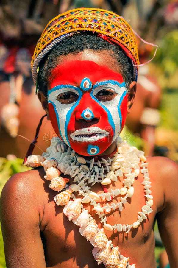 Sad face in Papua New Guinea. Hagen show, Papua New Guinea - circa August 2015: Young native boy during Hagen show, Papua New Guinea. Documentary editorial royalty free stock image