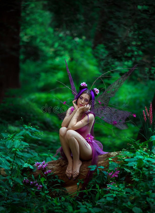 Sad fairy sitting on a tree. Fantastic photo shoot with smoke. Sad fairy sitting on a tree. Background fairy forest, vines and trees. Unusual fabulous views stock photo