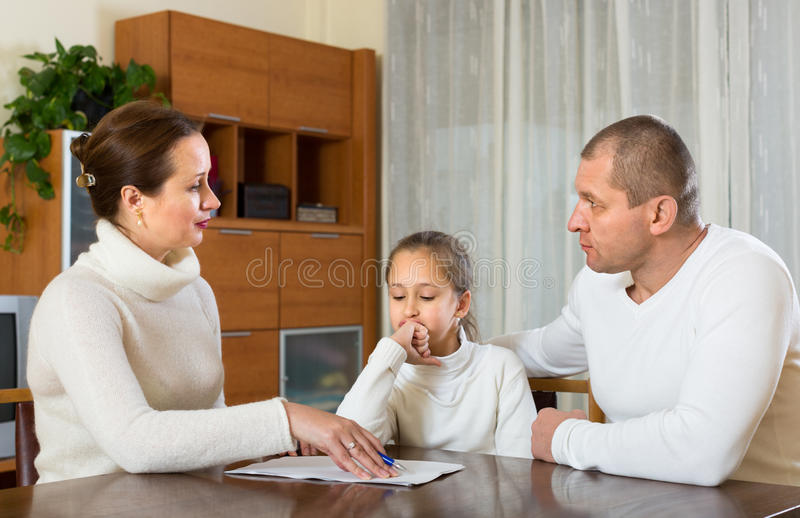 Sad family having financial problems. Sad family with daughter solving financial problems at the table at home royalty free stock photos