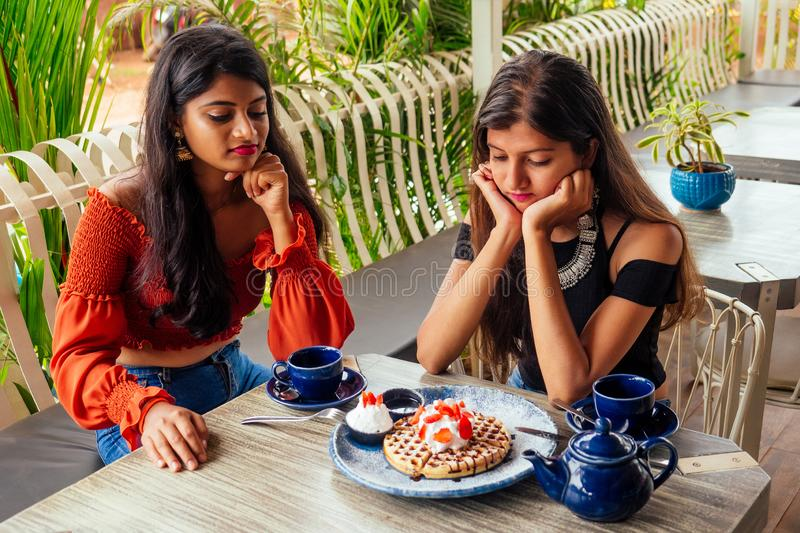 Sad fashionable indian friends couple of two woman looking at cakes.friends long-awaited meeting gossip students eating. Sad fashionable indian friends couple of stock photo