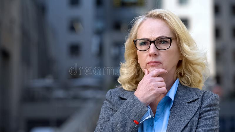 Sad female company worker thinking of work, worried business lady, pension age stock images