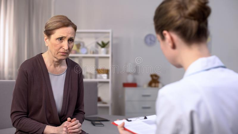 Sad female patient looking young doctor, feeling upset of bad diagnosis, health. Stock photo royalty free stock image