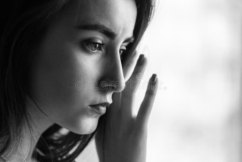Sad female portrait. Sensual sad closeup female portrait near window, monochrome royalty free stock photos