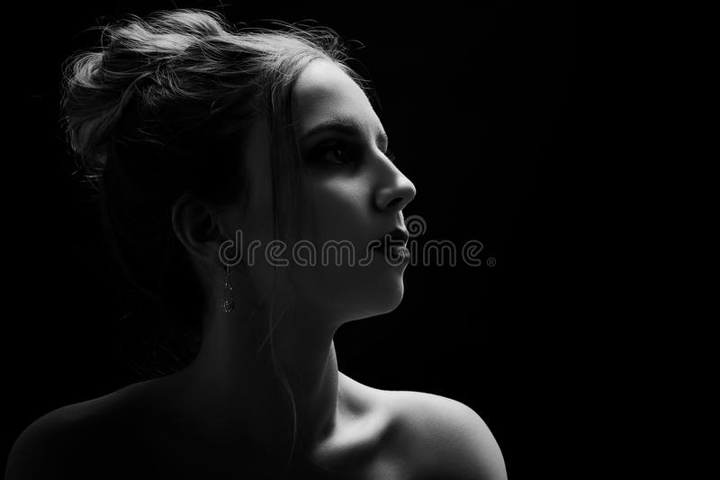 Sad female profile. On black background with copy space, monochrome royalty free stock images