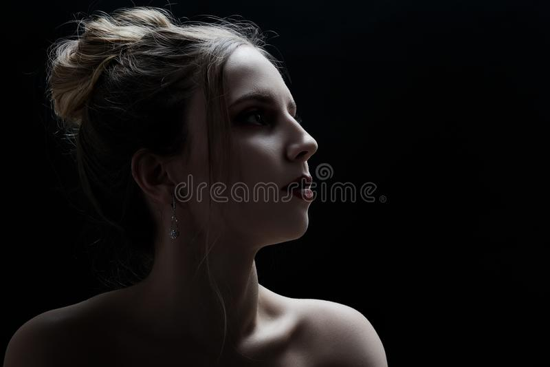 Sad female profile. On black background with copy space royalty free stock photo