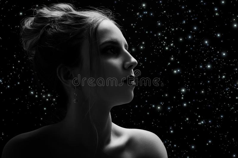 Sad female profile. On stars sky background with copy space, monochrome stock images