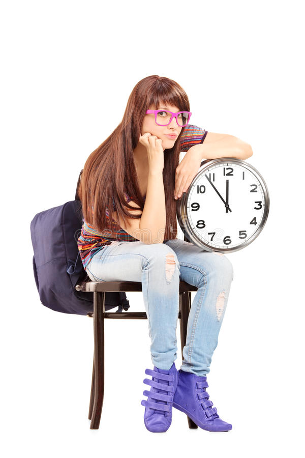 Sad female student sitting on a chair and holding a clock stock photography