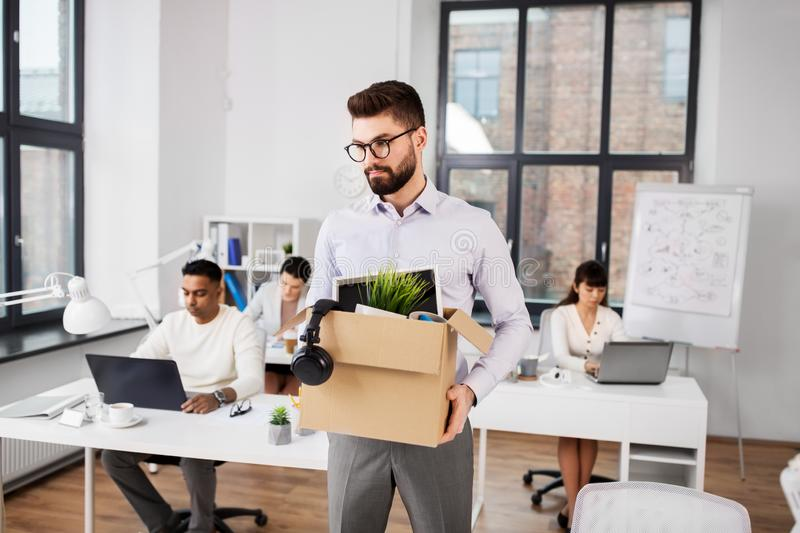 Sad fired male office worker with personal stuff royalty free stock photography