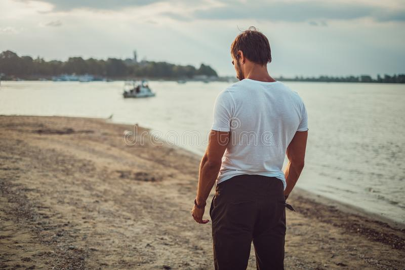 Sad fit man standing on the beach and looking down. In despair stock photos