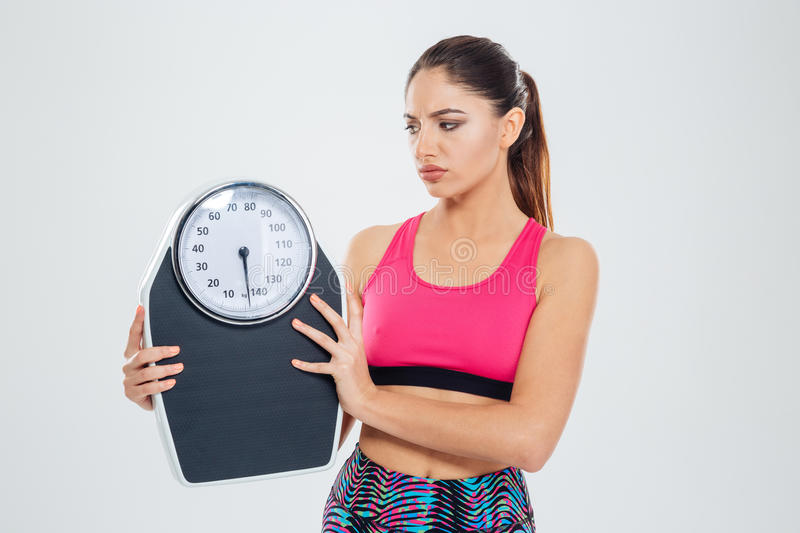 Sad fitness woman holding weighing machine. Isolated on a white background royalty free stock photos