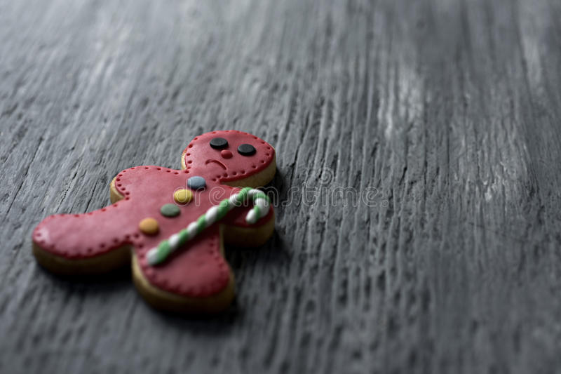 Sad gingerbread man. Closeup of a sad gingerbread man on a rustic wooden surface, with a negative space royalty free stock photos