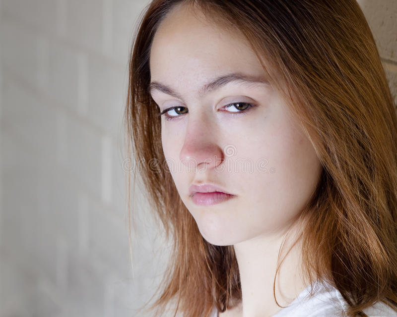 Sad girl. With brunette hair looking at the camera stock image