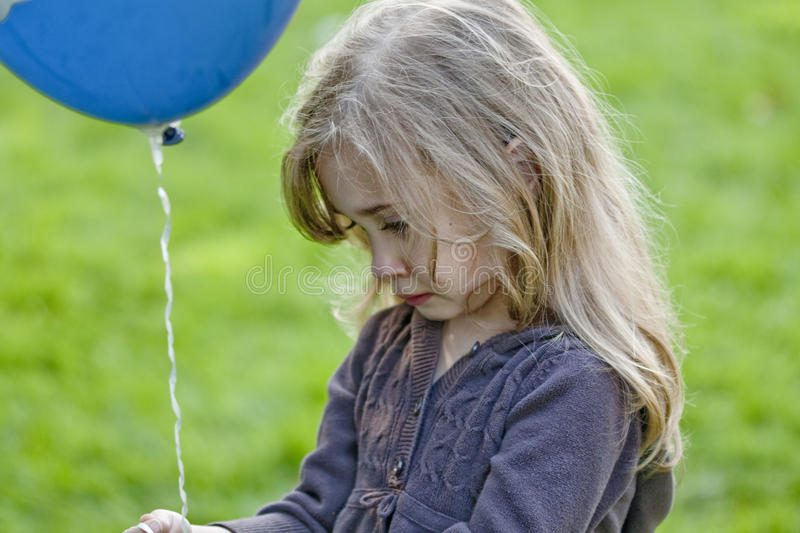 Sad girl with balloon. Portrait of sad preschool girl with balloon, grass, in background stock photo