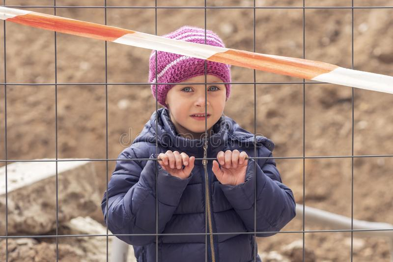 Sad girl behind the fence. Little beautiful girl on construction site behind fence with restrictive tape stock image