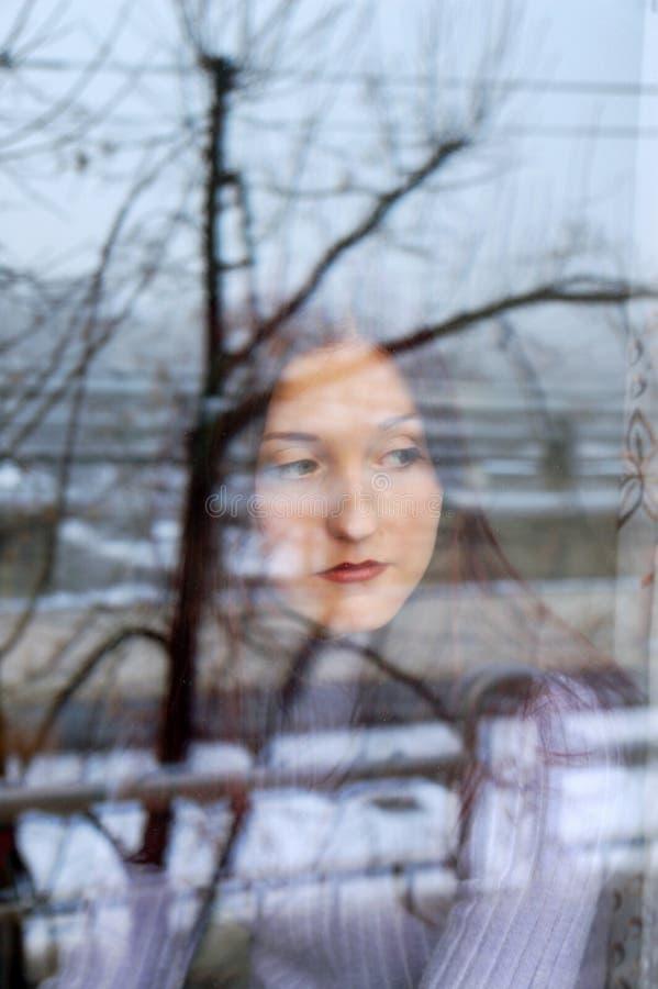 Sad girl behind the window