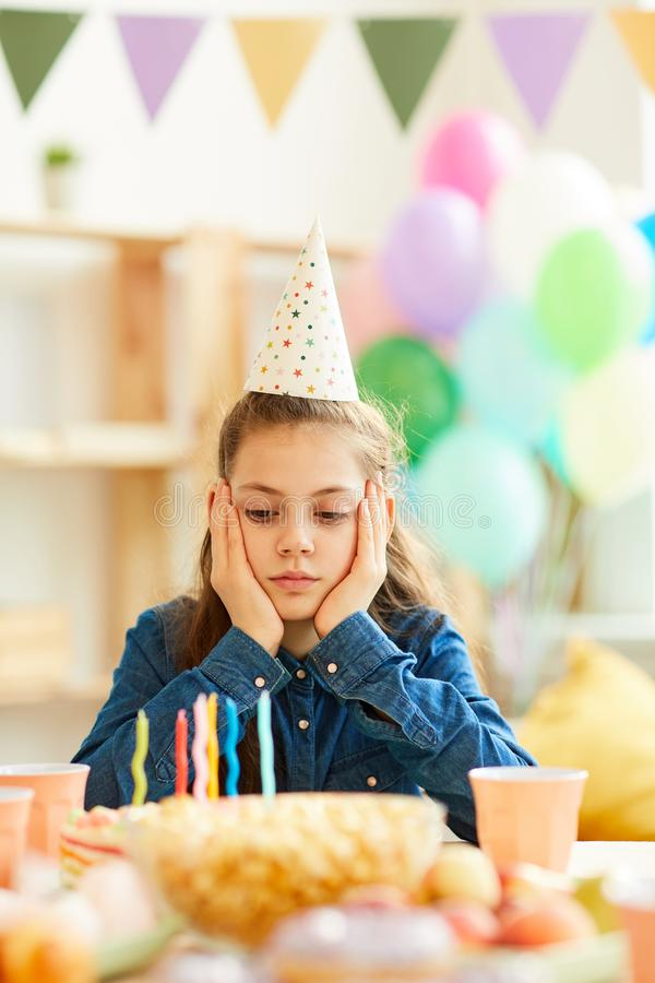 Sad Girl at Birthday Party. Portrait of sad teenage girl sitting alone at party table on her Birthday stock images