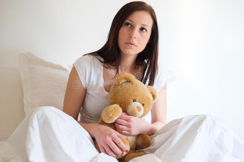 Sad girl getting lonely and hugging soft teddy bear stock photos