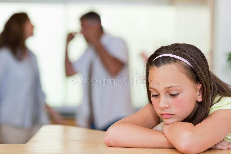 Sad girl with her fighting parents behind her royalty free stock image