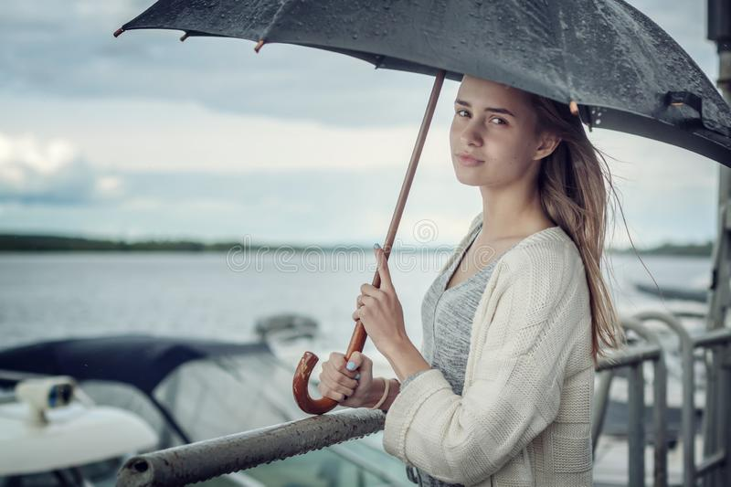 Sad girl hiding under a black umbrella from the rain, standing on the banks of the river. Curls of hair develop in the wind. Storm stock photo