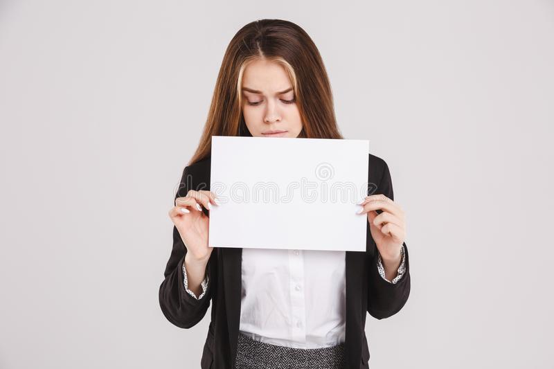 Sad girl holding an empty paper sheet suitable for text. Isolated on white background. Copy space stock image