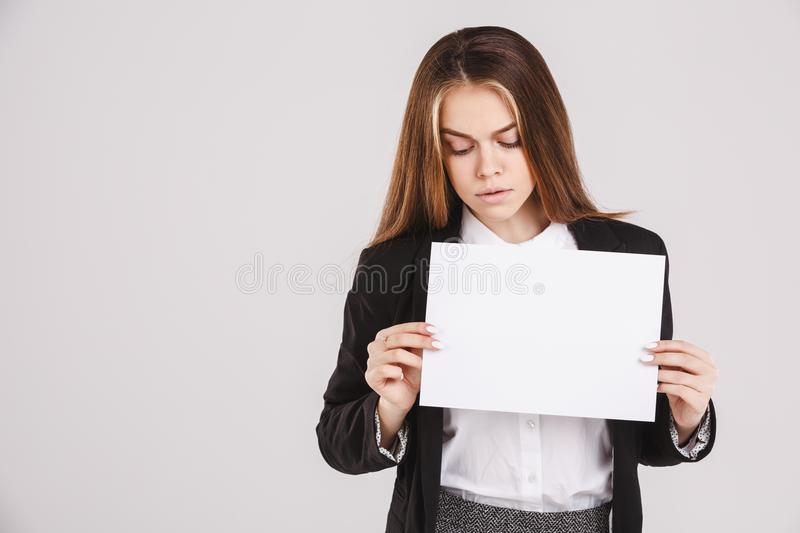 Sad girl holding an empty paper sheet suitable for text. Isolated on white background. Copy space royalty free stock images