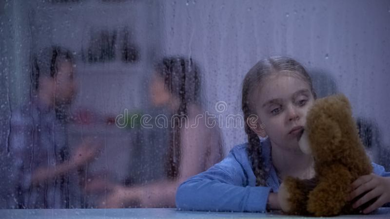 Sad girl holding teddy bear, parents conflicting, feeling stressed and insecure. Stock photo royalty free stock images