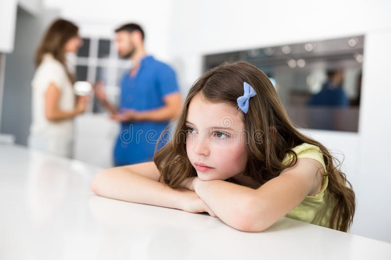Sad girl leaning on table against arguing parents royalty free stock images