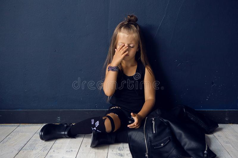 Sad girl in a leather jacket rock home sitting. On white floor royalty free stock photos