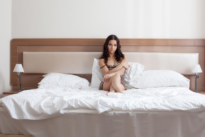 Sad Girl In Leopard Print Negligee Lying On Bed Royalty Free Stock Photography