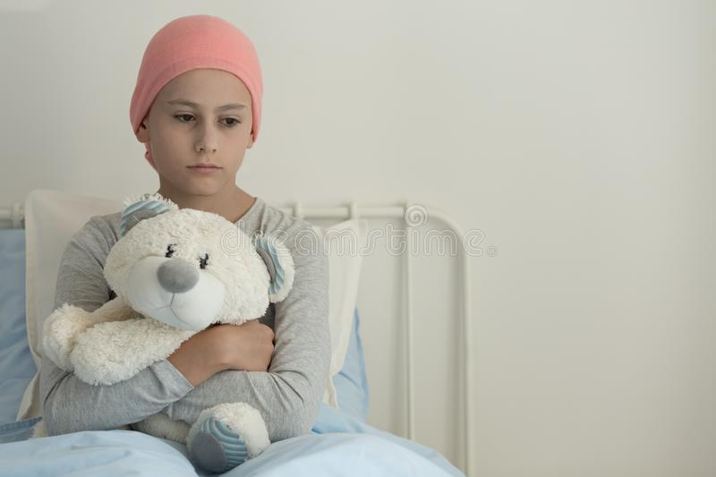 Sad girl with leukemia hugging plush toy in the hospital. With copy space stock photo