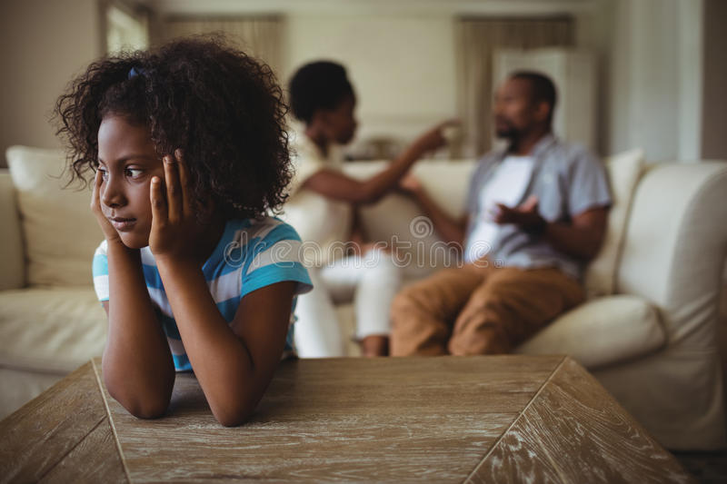 Sad girl listening to her parents arguing stock photography