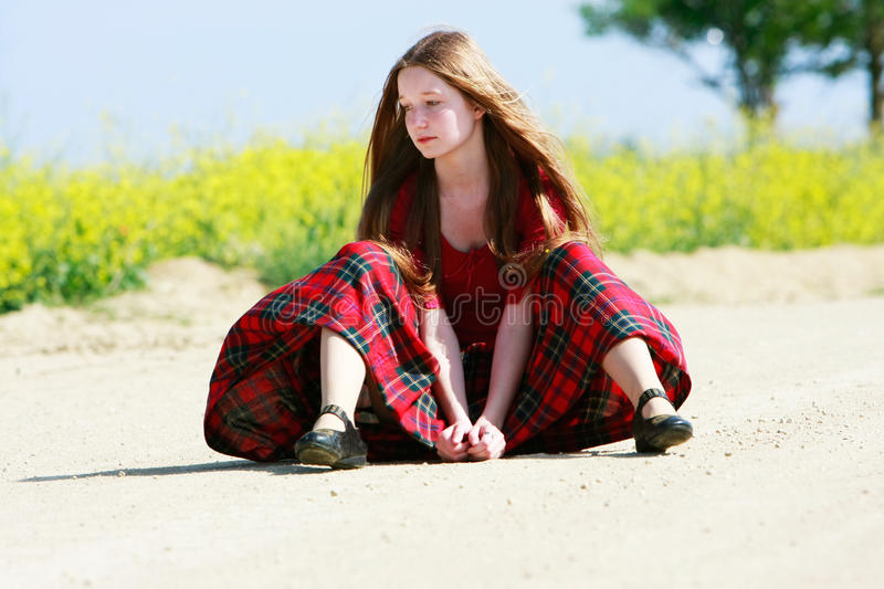 Sad girl with long hair on country road stock photography