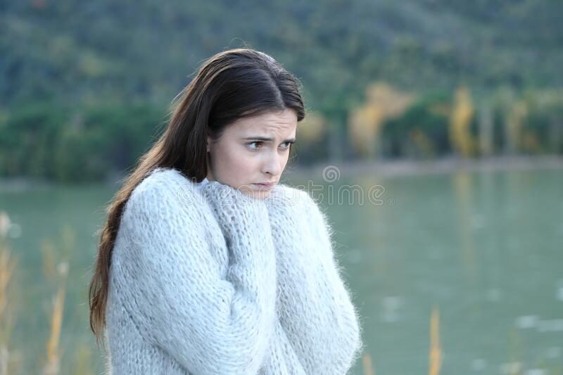 Sad girl looking away in a lake in winter royalty free stock photo