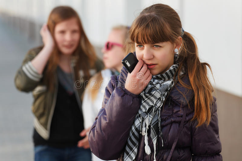 Sad teen girl with a mobile phone royalty free stock image