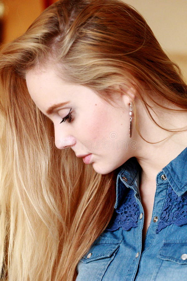 Sad girl in profile, spreading hairs, in a denim shirt. Beautiful blonde with a fresh face, in profile, with a beautifully flowing hair royalty free stock images