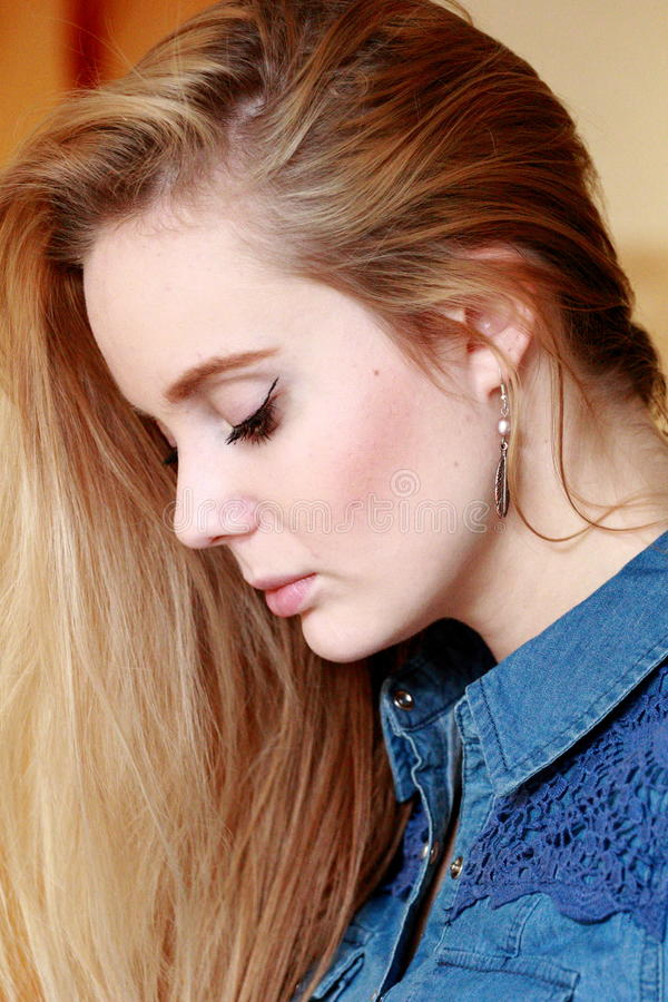 Sad girl in profile, spreading hairs, in a denim shirt. Beautiful blonde with a fresh face, in profile, with a beautifully flowing hair stock image
