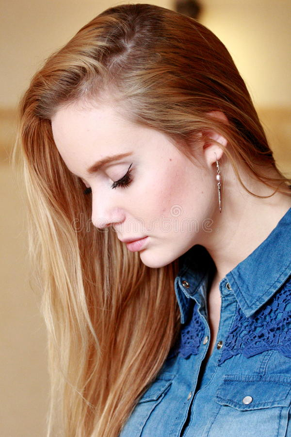 Sad girl in profile, spreading hairs, in a denim shirt. Beautiful blonde with a fresh face, in profile, with a beautifully flowing hair royalty free stock photo