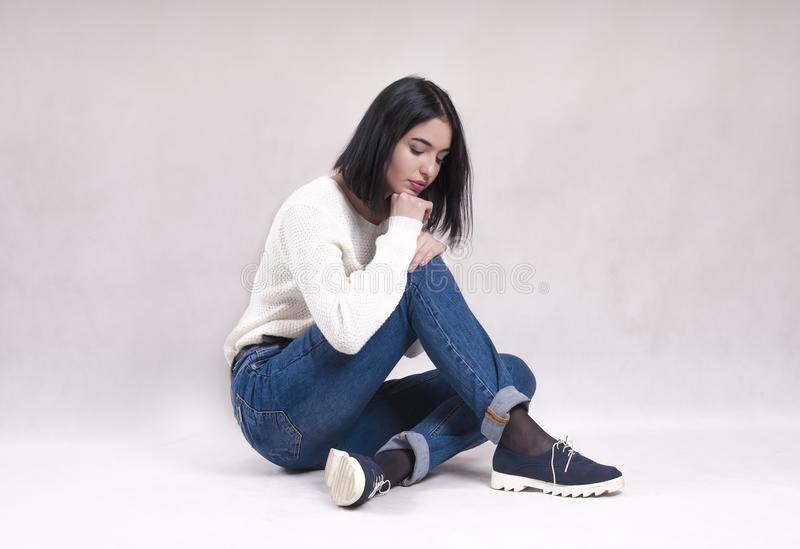 Sad girl sits on the floor in jeans news depression difficulties. Sad girl sits on the floor in jeans news depression stock photography