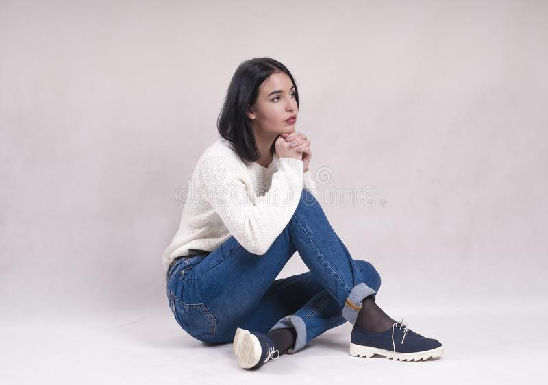 Sad girl sits on the floor in jeans news depression solitude difficulties. Sad girl sits on the floor in jeans news depression solitude stock photos