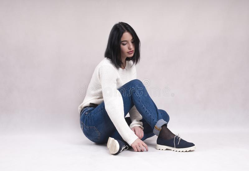 Sad girl sits on the floor in jeans loneliness news depression solitude difficulties. Sad girl sits on the floor in jeans news depression solitude loneliness royalty free stock photos