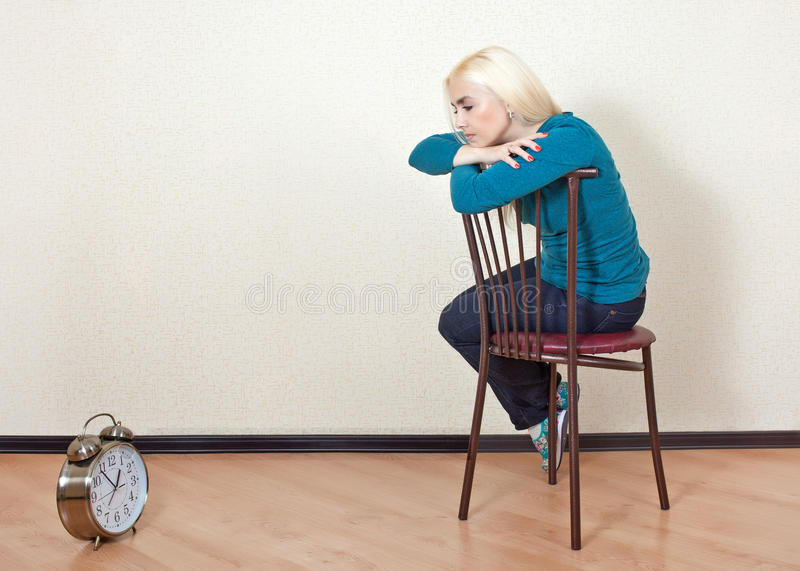 Download Sad Girl Sitting On A Chair And Looks At His Watch Stock Image - Image & Sad Girl Sitting On A Chair And Looks At His Watch Stock Image ...