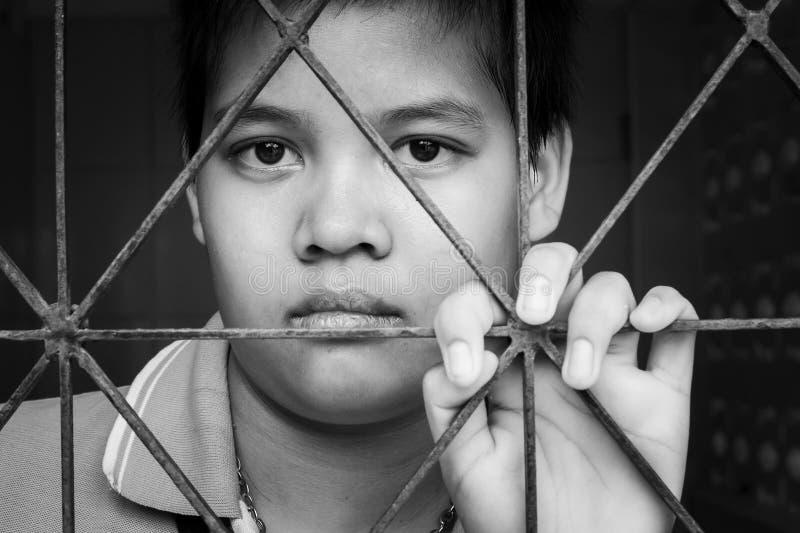 Sad girl standing alone behind jail bars. Girl standing alone behind jail bars stock photo