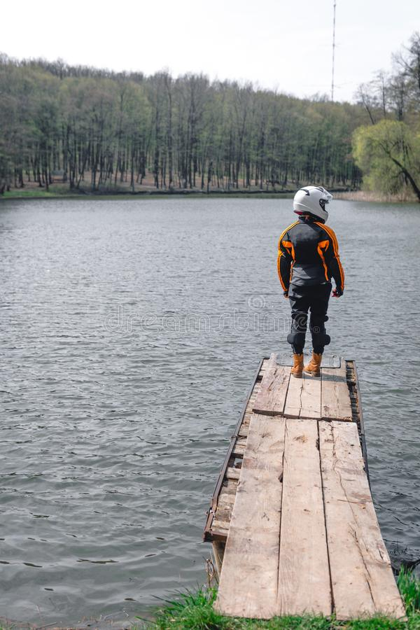A sad girl is standing alone on the pier by the lake. Forest background. wearing in motorcycle outfit protection equipment. stock image