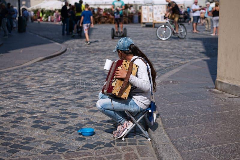 Sad girl street musician playing small accordion royalty free stock photo