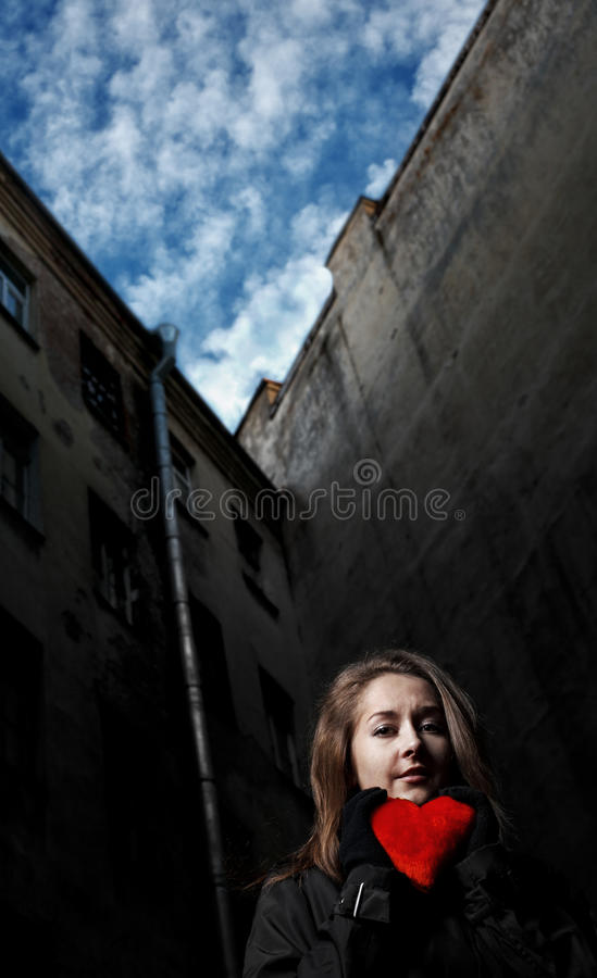 Sad girl with toy heart royalty free stock image