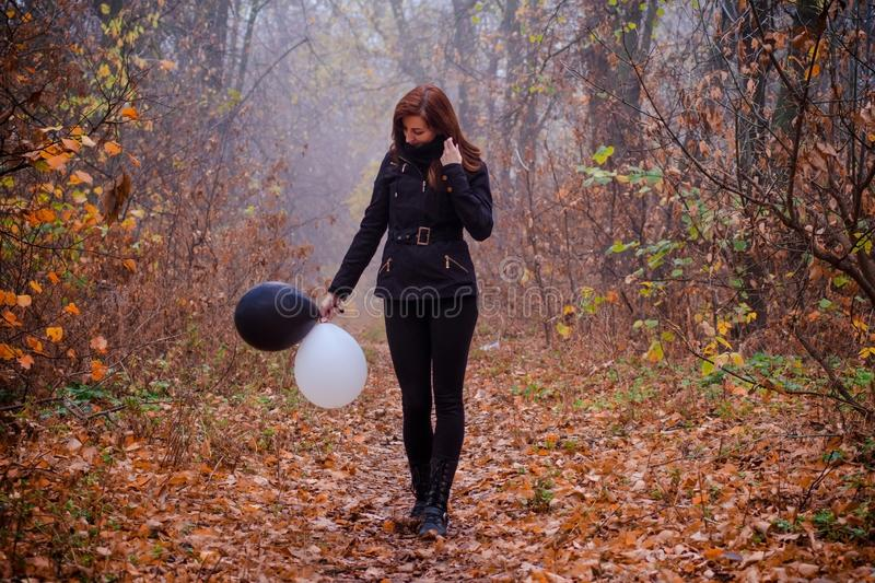 Sad girl walking in dark clothing in autumn forest, with balloons, black and white. Concept of choice, good and evil royalty free stock image