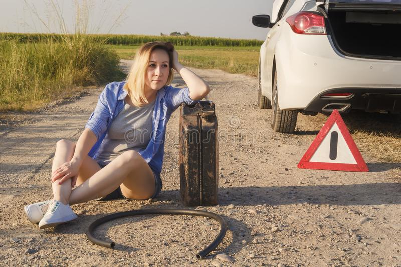 Sad girl whose driver has run out of gasoline in a car on a rural road sits waiting for help with a fuel canister and a hose royalty free stock images