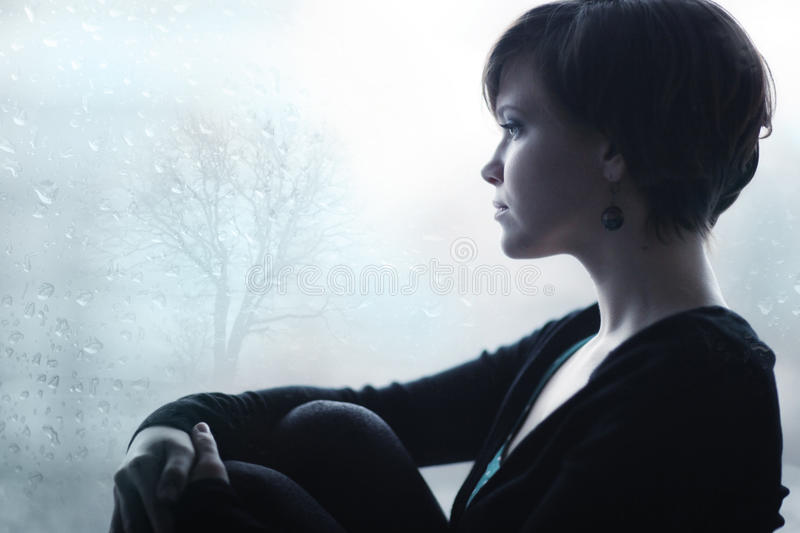 Sad girl on the windowsill looking out window. Sad girl on the windowsill looking out the window royalty free stock image