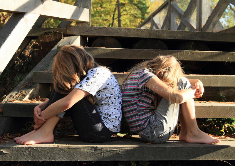Sad girls sitting on stairs. Two barefoot girls - sad crying kids sitting on wooden stairs royalty free stock photos