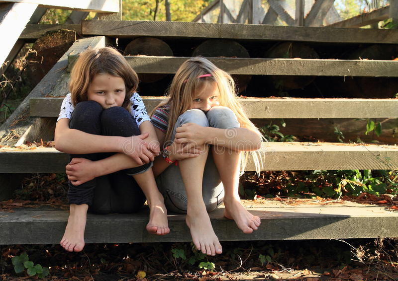 Sad girls sitting on stairs. Two barefoot girls - sad crying kids sitting on wooden stairs stock images